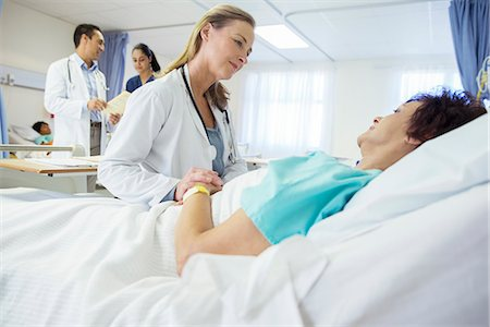 Doctor talking to patient in hospital bed Stock Photo - Premium Royalty-Free, Code: 6113-07762002