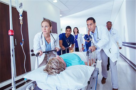 patient walking hospital halls - Doctors and nurses wheeling patient down hospital hallway Stock Photo - Premium Royalty-Free, Code: 6113-07762035