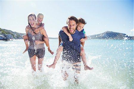 Family running in water on beach Stock Photo - Premium Royalty-Free, Code: 6113-07762162