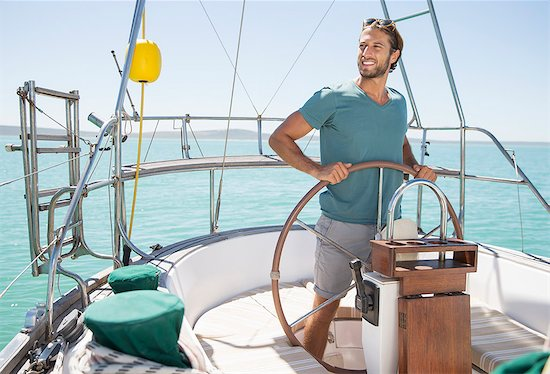 Man steering sailboat on water Stock Photo - Premium Royalty-Free, Image code: 6113-07762166