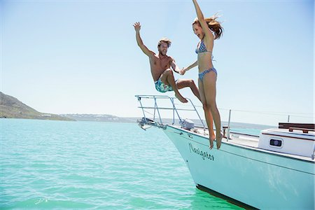 Couple jumping off boat together Stock Photo - Premium Royalty-Free, Code: 6113-07762171