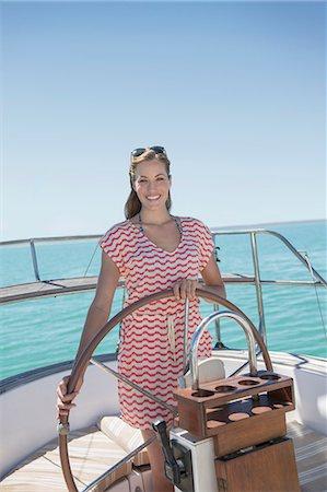 sailboat  ocean - Woman steering sailboat on water Stock Photo - Premium Royalty-Free, Code: 6113-07762181