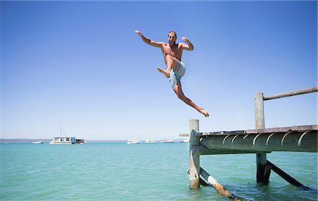 Couple jumping off wooden dock into water Stock Photo - Premium Royalty-Free, Code: 6113-07762120