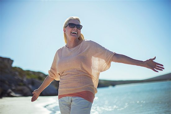 Older woman smiling in sun on beach Stock Photo - Premium Royalty-Free, Image code: 6113-07762121