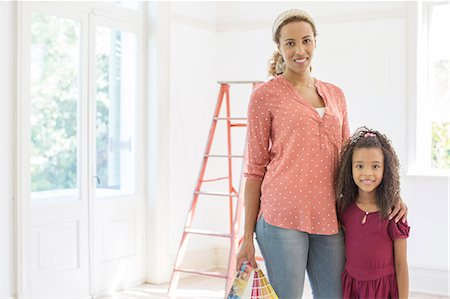 Mother and daughter smiling in living space Stock Photo - Premium Royalty-Free, Code: 6113-07762249