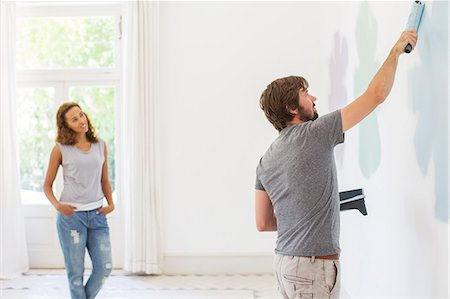 paint - Man painting wall with girlfriend observing Stock Photo - Premium Royalty-Free, Code: 6113-07762259