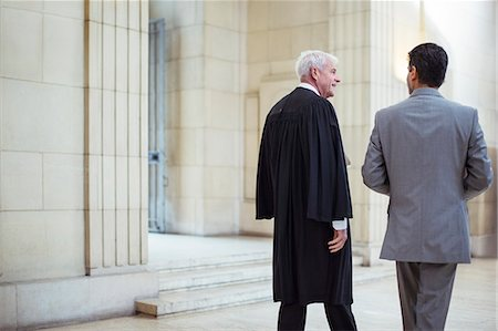 Judge and lawyer walking through courthouse together Stock Photo - Premium Royalty-Free, Code: 6113-07762352