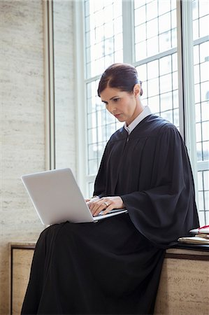 Judge sitting on bench using laptop in courthouse Stock Photo - Premium Royalty-Free, Code: 6113-07762361