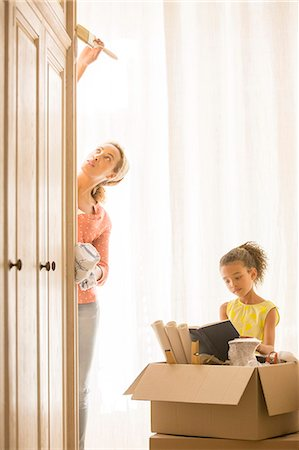 Mother painting wardrobe with daughter reading Stock Photo - Premium Royalty-Free, Code: 6113-07762303