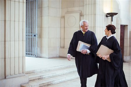 Judges walking through courthouse together Stock Photo - Premium Royalty-Free, Code: 6113-07762332