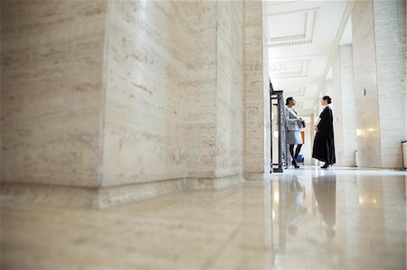 Lawyer and judge talking in hallway of courthouse Stock Photo - Premium Royalty-Free, Code: 6113-07762335