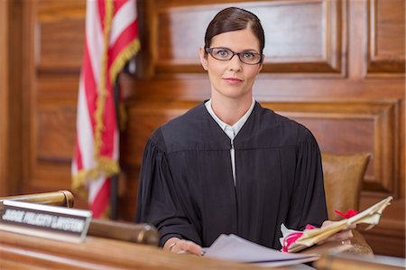 Judge examining documents at judges bench in court Stock Photo - Premium Royalty-Free, Code: 6113-07762456