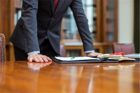 Lawyer leaning on table in chambers Stock Photo - Premium Royalty-Free, Code: 6113-07762410
