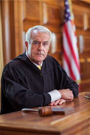 Judge sitting at judges bench in court Stock Photo - Premium Royalty-Free, Code: 6113-07762424