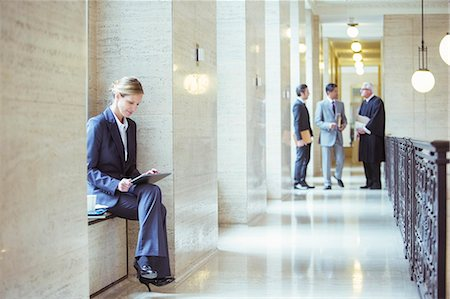 Lawyer working on digital tablet in courthouse Stock Photo - Premium Royalty-Free, Code: 6113-07762433