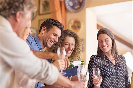 Man pouring drinks to family members Stock Photo - Premium Royalty-Free, Code: 6113-07762566