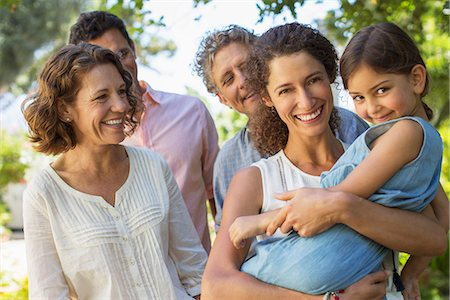 Mother carrying daughter in arms with family outdoors Stock Photo - Premium Royalty-Free, Code: 6113-07762589
