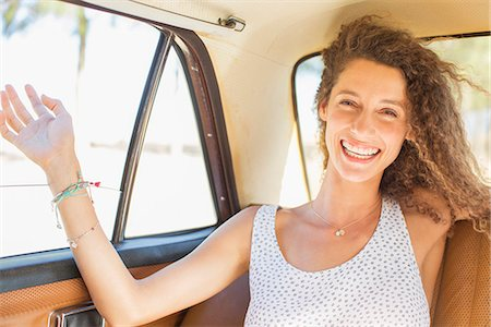 Woman feeling breeze from backseat car window Stock Photo - Premium Royalty-Free, Code: 6113-07762622