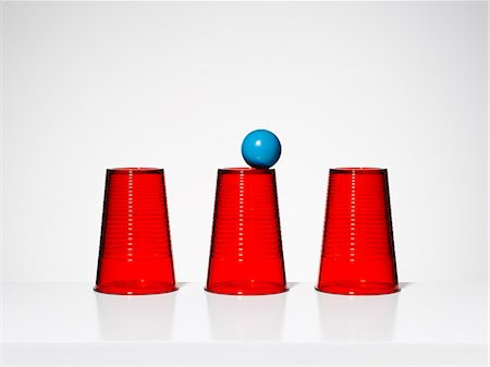 Blue ball balancing on middle of three red cups Stock Photo - Premium Royalty-Free, Code: 6113-07790182