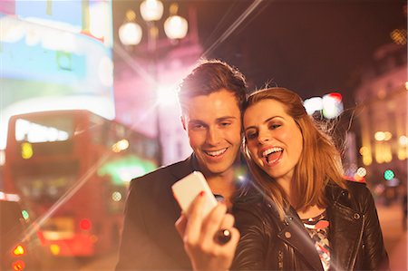 Couple taking cell phone picture together on city street at night Stock Photo - Premium Royalty-Free, Code: 6113-07790272