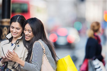 shop - Women looking at cell phone on city street Stock Photo - Premium Royalty-Free, Code: 6113-07790283