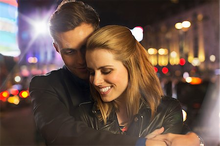 Couple hugging on city street at night Stock Photo - Premium Royalty-Free, Code: 6113-07790298