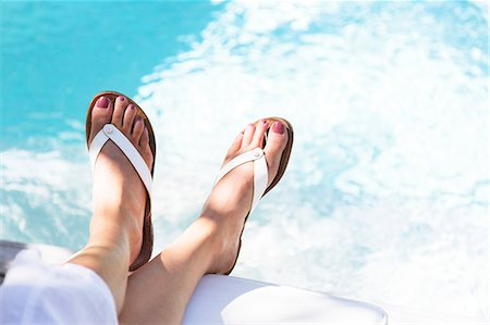dangling - Close up of woman's feet dangling over swimming pool Stock Photo - Premium Royalty-Free, Code: 6113-07790497