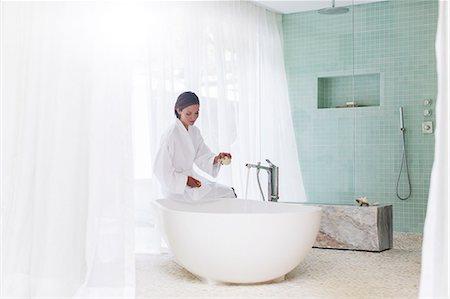 Woman running bath in modern bathroom Stock Photo - Premium Royalty-Free, Code: 6113-07790499