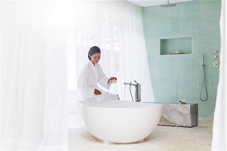 rich lifestyle - Woman running bath in modern bathroom Stock Photo - Premium Royalty-Free, Code: 6113-07790499