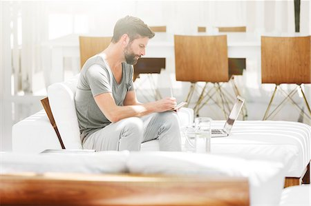 rich lifestyle - Man writing notes at laptop on sofa in modern living room Stock Photo - Premium Royalty-Free, Code: 6113-07790547