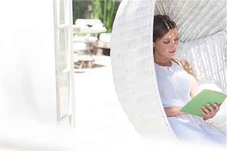 dangling - Woman reading book in hanging wicker chair outdoors Stock Photo - Premium Royalty-Free, Code: 6113-07790551