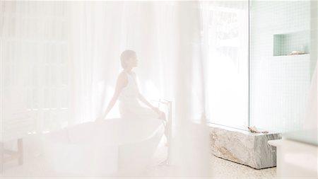 Woman in modern bathroom viewed through sheer curtain Stock Photo - Premium Royalty-Free, Code: 6113-07790559
