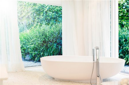 Bathtub, curtains, and windows in modern bathroom Stock Photo - Premium Royalty-Free, Code: 6113-07790574