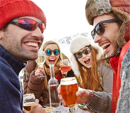 Friends celebrating with drinks in snow Stock Photo - Premium Royalty-Free, Code: 6113-07790581