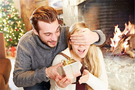 sweater and fireplace - Couple exchanging gifts on Christmas Stock Photo - Premium Royalty-Free, Code: 6113-07790591