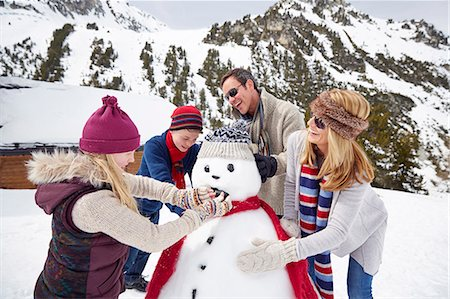 Family building a snowman together Stock Photo - Premium Royalty-Free, Code: 6113-07790595