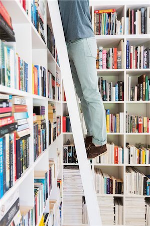 Man standing on ladder to reach books in library Stock Photo - Premium Royalty-Free, Code: 6113-07790503