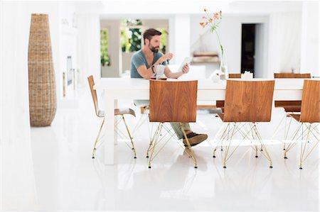 Man using digital tablet at breakfast table in modern dining room Stock Photo - Premium Royalty-Free, Code: 6113-07790512