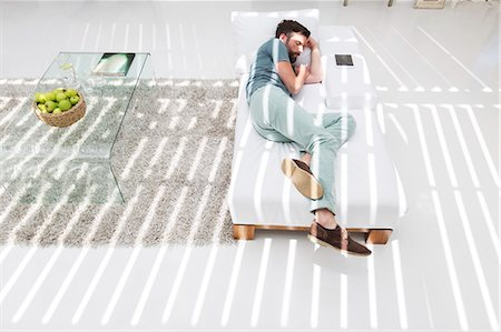 picture - Man napping on daybed in modern living room Stock Photo - Premium Royalty-Free, Code: 6113-07790520