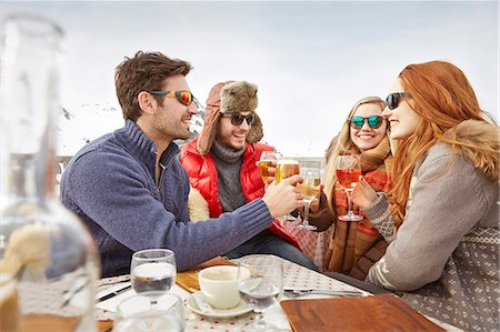 Friends celebrating with drinks in the snow Stock Photo - Premium Royalty-Free, Code: 6113-07790652