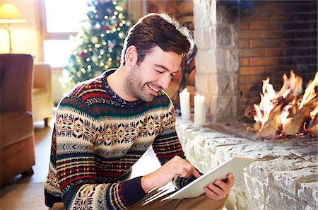 sweater and fireplace - Man using digital tablet in front of fireplace Stock Photo - Premium Royalty-Free, Code: 6113-07790665