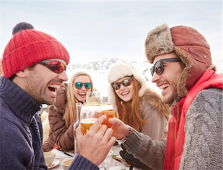 Friends celebrating with drinks in the snow Stock Photo - Premium Royalty-Free, Code: 6113-07790603