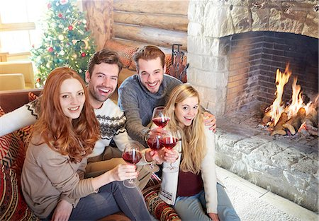 sweater and fireplace - Friends celebrating with drinks in log cabin Stock Photo - Premium Royalty-Free, Code: 6113-07790604