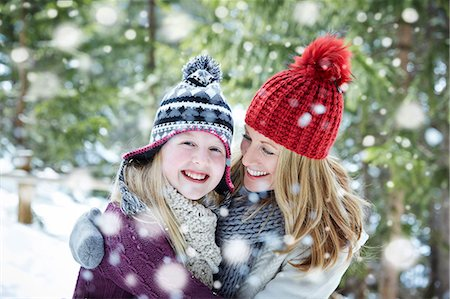snowflakes  holiday - Mother and daughter hugging in the snow Stock Photo - Premium Royalty-Free, Code: 6113-07790622