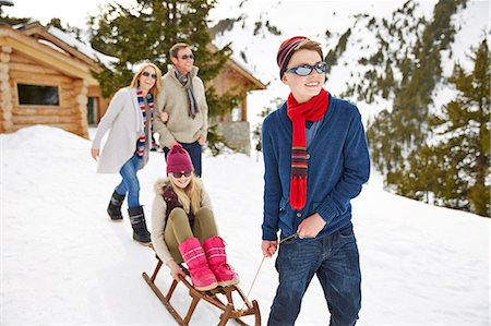 pulling - Brother pulling sister on sledge in snow Stock Photo - Premium Royalty-Free, Code: 6113-07790630