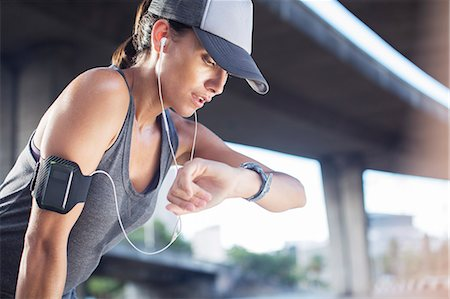 Woman looking at watch after exercising on city street Stock Photo - Premium Royalty-Free, Code: 6113-07790799
