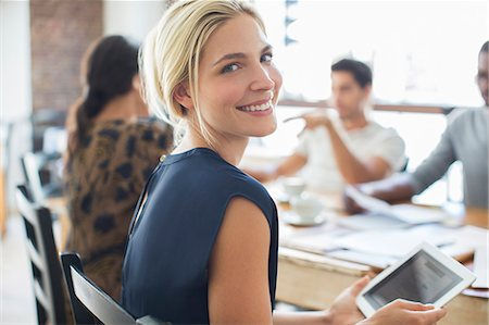 Businesswoman using digital tablet at meeting in cafe Stock Photo - Premium Royalty-Free, Code: 6113-07790870