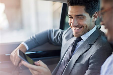 Businessmen looking at cell phone in car Stock Photo - Premium Royalty-Free, Code: 6113-07790888