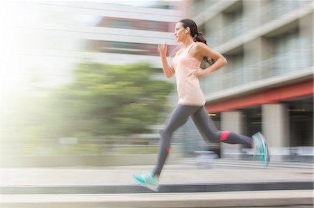Woman running through city streets Stock Photo - Premium Royalty-Free, Code: 6113-07790808