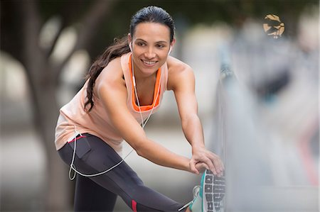Woman stretching before exercising on city street Stock Photo - Premium Royalty-Free, Code: 6113-07790818